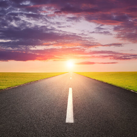 end of the line: Driving on an empty road against the rising sun Stock Photo