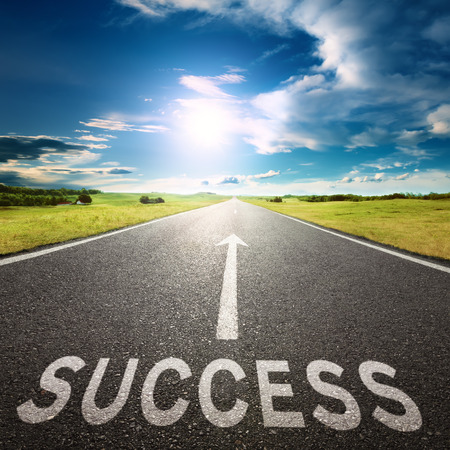 road signs: Empty asphalt road towards the sun and sign symbolizing success  Stock Photo