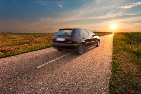 Black car in motion blur on the road towards the setting sun photo