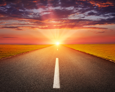 open road: Driving on an empty asphalt road through the agricultural fields at sunset Stock Photo