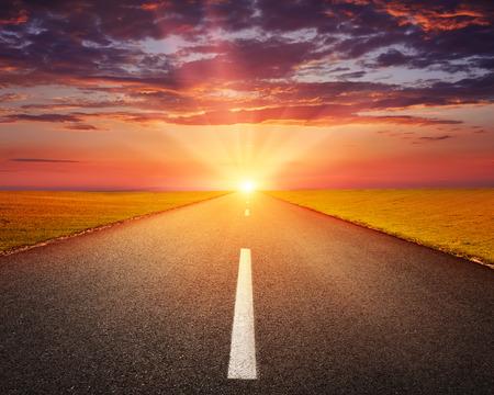 Rijden op een lege asfaltweg door de akkers bij zonsondergang Stockfoto