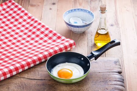 One fried egg in a pan, served in retro style photo