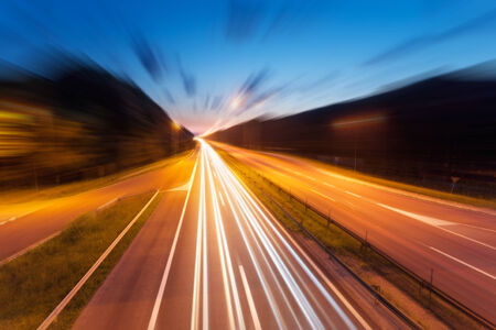 Long exposure photo on a highway with light trails at dusk in blurred motion photo