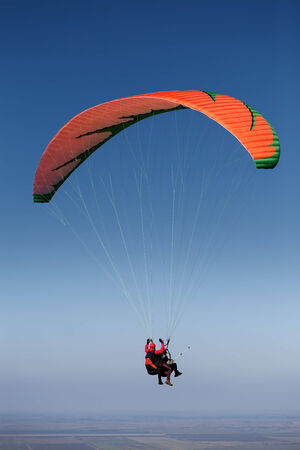 Risk Free: Two paragliders in flight above the vast plain