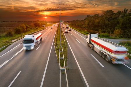 Two white trucks - cistern in motion blur on the highway at sunset