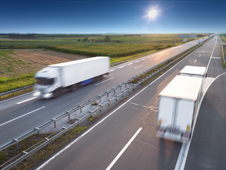 Two white trucks in motion blur on highway at sunny day near Belgrade - Serbia