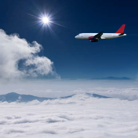 above the clouds: White airplane flying at high altitude above the clouds against the the sun