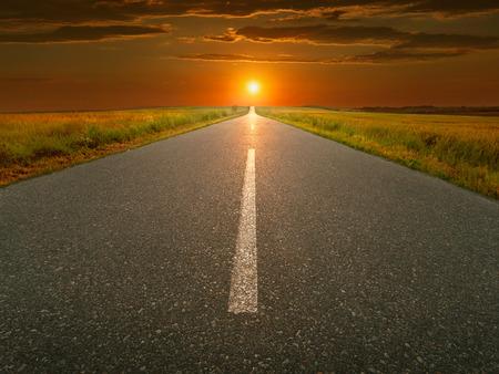 back roads: Empty open road towards the setting sun. Stock Photo