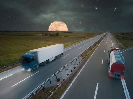Two trucks in motion blur on the highway at night of the full moon