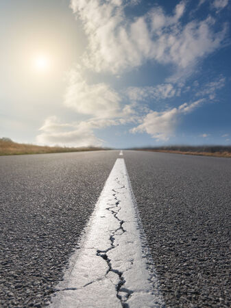Driving on an empty road at sunny day. Focus on the beginning of the asphalt road
