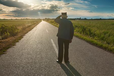 De hogere landbouwer die zich in het midden van de weg bevindt en overziet naar de zon op ongebruikelijke zonnestraal