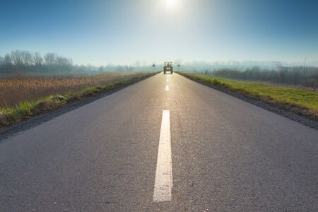 road tractor: Driving on asphalt road towards the rising sun and upcoming tractor. Stock Photo