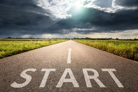 Rijden op een lege asfaltweg door de akkers bij zonnige dag. Concept visie voor een nieuw begin met een bord start en een pijl in de richting van de zon.