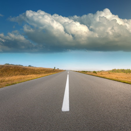Driving on an empty asphalt road through the idyllic fields at sunny day, against the big threatening cloud. Stock Photo