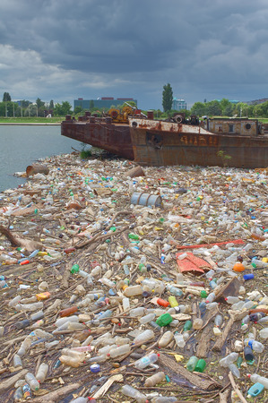polluting: Polluted river bank full of rubbish and garbage towards the new, modern, urban city area.