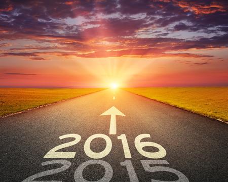 Das Fahren auf einer leeren Straße in Richtung der untergehenden Sonne zu bevor 2016 und hinterließ alten 2015. Standard-Bild - 37044051