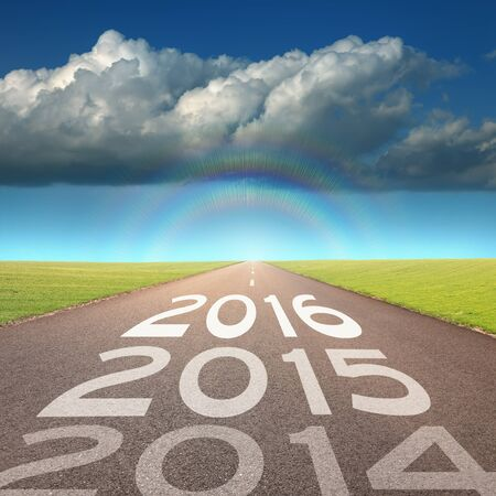 Driving on an empty road towards the big cloud and rainbow to upcoming 2016 and leaving behind old 2015 and 2014.