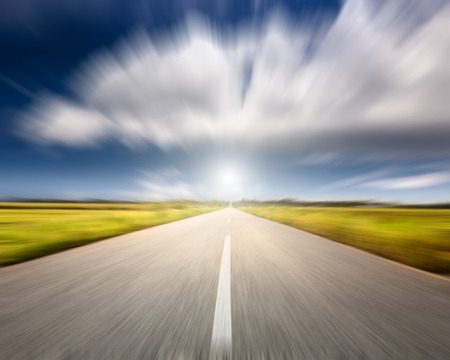 Driving on an empty road towards the big cloud at beautiful sunny day in motion blur Banco de Imagens