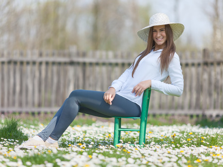 grassy field: Young girl with a straw hat sitting in a chair, in the idyllic nature flourish grassy field, enjoying the first rays of spring sunshine. Shallow depth of field. Stock Photo