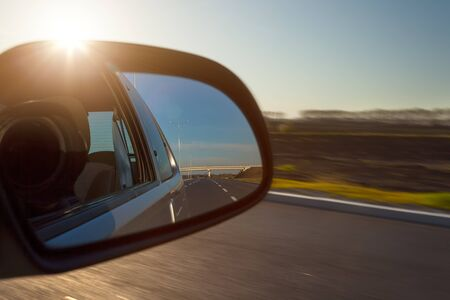Photographing from a car at high speed from the side towards the rearview mirror and the setting sun Banco de Imagens