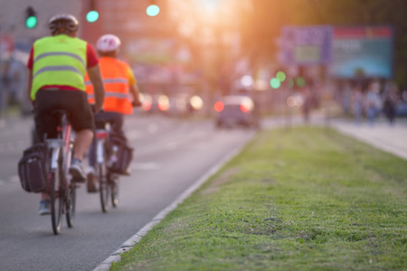 Two cyclists with protective equipment are approaching an intersection in a busy part of the city towards the setting sun. Shallow depth of field, focus on the grass in the foreground.