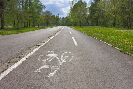 bicycle lane: Bicycle lane with white bicycle sign at city park in back light. Stock Photo