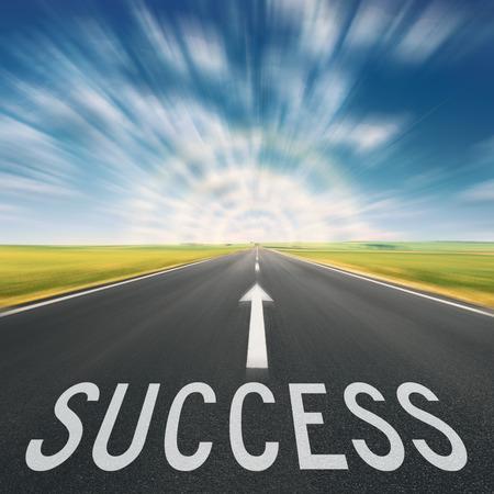 mision: Conducir en una carretera de asfalto vacía en el movimiento borroso, hacia la luz y el signo que simboliza el éxito. Concepto para el éxito.