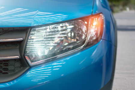 Blue modern car closeup of headlight. Exterior detail, shallow depth of field. Banco de Imagens