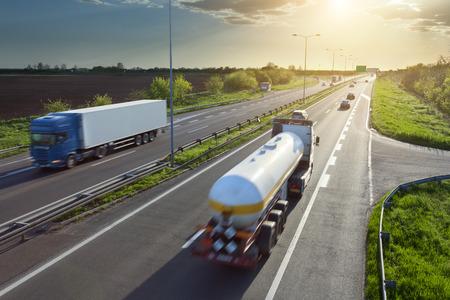 camión: Dos camiones en movimiento borroso en la autopista hacia el sol poniente. Hora punta en la autopista cerca de Belgrado - Serbia. Foto de archivo