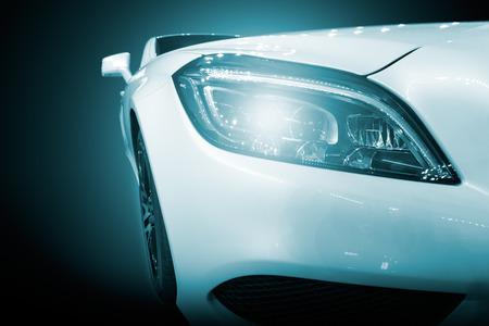 front view: White modern car closeup of headlight. Exterior detail, shallow depth of field.