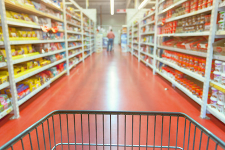 isle: Shopping concept in supermarket for fast consumer lifestyle. Shopping cart in in blurred motion through the aisles.