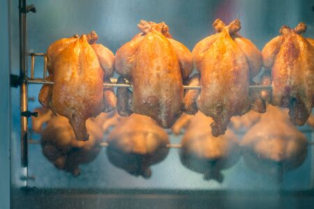 chicken grill: Grilled roasted chickens on a spit in rotisserie near the butcher shop. Shallow depth of field.