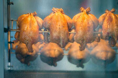 pollo rostizado: La parrilla pollos asados ??en un asador en asador cerca de la carnicería. Poca profundidad de campo.