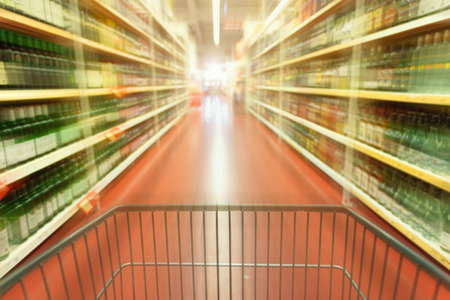 Shopping concept in supermarket for fast consumer lifestyle. Shopping cart in in blurred motion through the aisles. photo