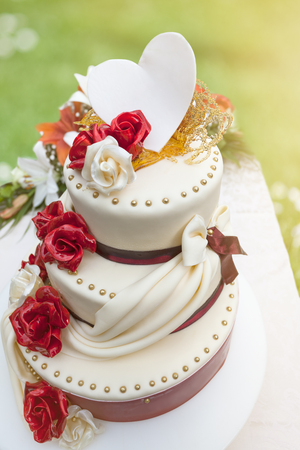 wedding heart: Elegant wedding cake on three floors with edible decoration in the shape of roses, ribbons and heart in nature environment, illuminated by the sunlight.