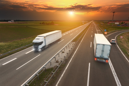 Two white trucks driving in motion blur on the freeway towards the setting sun. Rush hour on the motorway near Belgrade - Serbia.