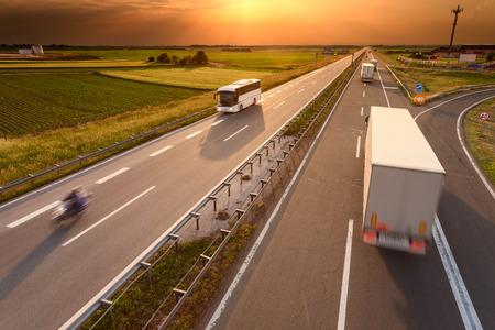 LKW, Bus und Motorrad fahren in Bewegungsunschärfe auf der Autobahn in Richtung der untergehenden Sonne. Hauptverkehrszeit auf der Autobahn in der Nähe von Belgrad - Serbien.