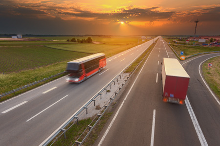 red traffic light: Truck and bus driving in motion blur on the freeway towards the setting sun. Rush hour on the highway near Belgrade - Serbia. Stock Photo
