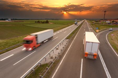 llanura: Muchos camiones en movimiento borroso en la autopista hacia el sol poniente. Hora punta en la autopista cerca de Belgrado - Serbia. Foto de archivo