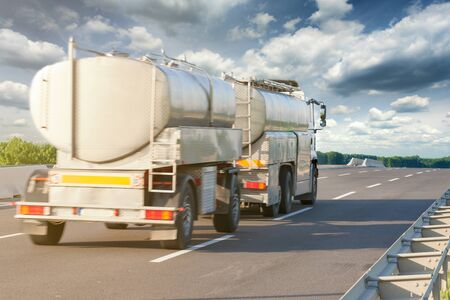 Rear view to truck tank of milk on highway at sunny day.