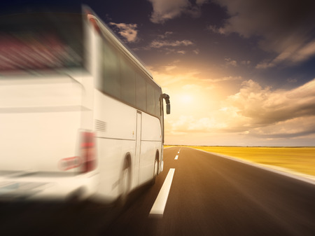 White bus in speed driving on an empty open road towards the setting sun in blurred motion.