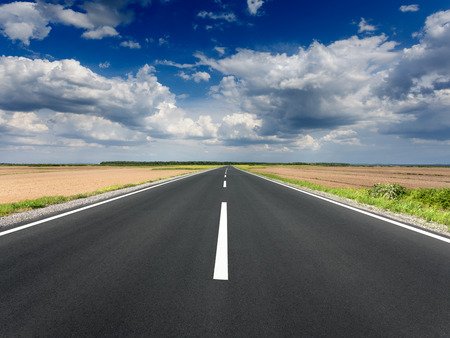 Driving on an open asphalt road through the agricultural fields at idyllic sunny day. Imagens