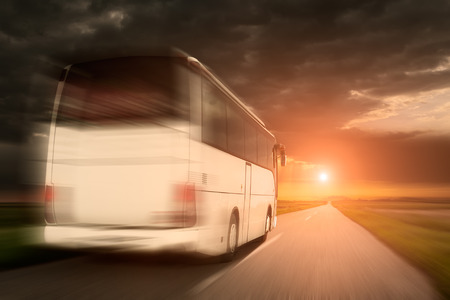 open road: White bus in fast driving on an empty open road towards the setting sun in blurred motion.