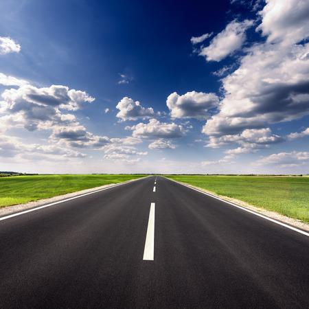 route: Conduire sur une route goudronnée vide à travers les champs verts agricoles à journée ensoleillée idyllique. Banque d'images