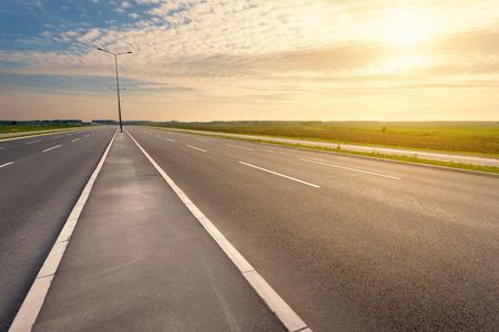 asphalt: Driving on an empty asphalt six lane highway through the cultivated fields towards the setting sun.