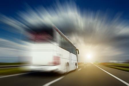 transportation: Bus blanc en mouvement flou à pleine vitesse effectue dépassements sur l'autoroute. Photographié de la voiture lors de la conduite.
