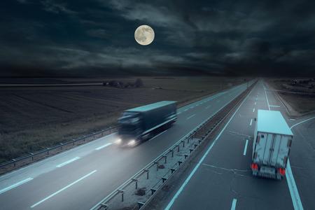 Blaue und weiße LKW in Motion Blur auf der Autobahn in der Nacht mit Mond. Standard-Bild - 44653305