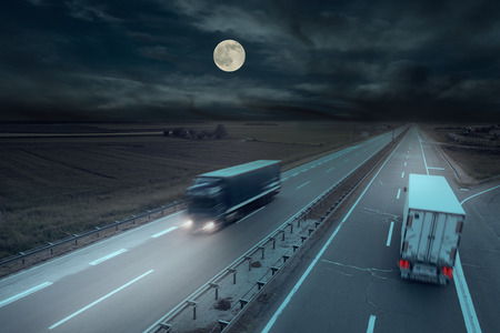 Blue and white truck in motion blur on the highway at night with moon.