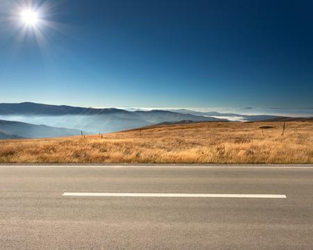 경치: 빈 아스팔트 도로와 목가적 인 화창한 날에 배경 흐린 산의 측면보기.
