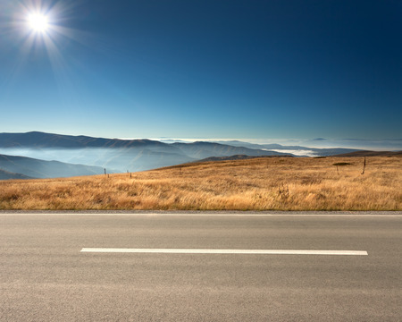 Vista lateral da estrada de asfalto vazio e montanhas nebuloso no fundo no dia ensolarado idílico. Imagens